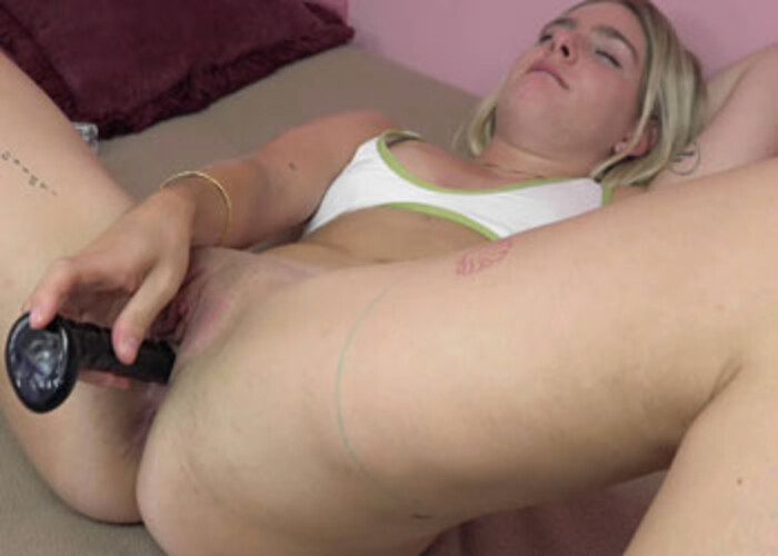 Opal slips a glass dildo into her vagina
